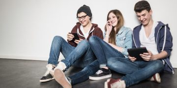 Three teenagers sitting on floor using technology