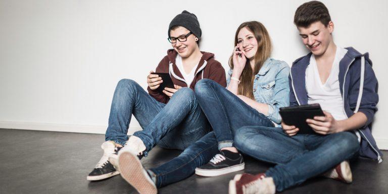 Three teenagers sitting on floor using technology